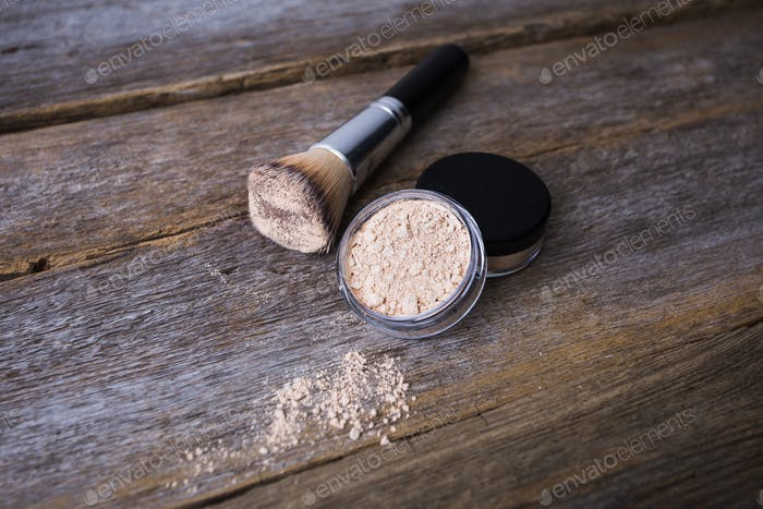 mineral powder of different colors with a brush for make-up on wooden background