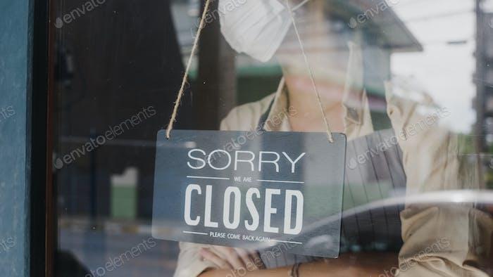 Joven Asia chica usar máscara facial girando un signo de abierto a cerrado signo en la puerta de vidrio café