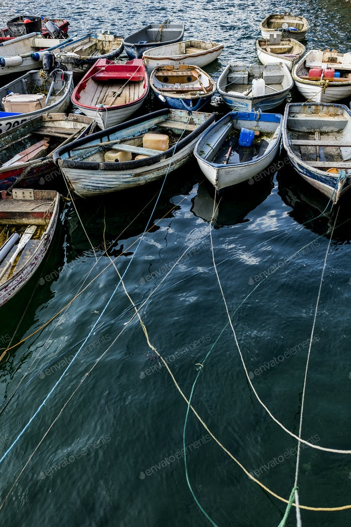 High angle view of colourful wooden fishing boats moored side by side in an harbour.