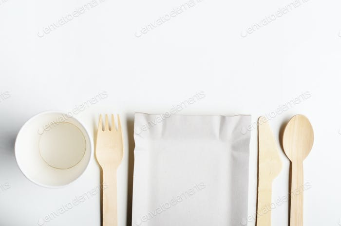 Wooden single use kitchenware and paper cups and plates on white