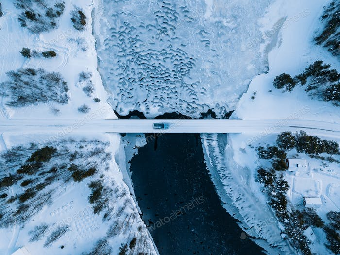 Aerial top view of bridge road above frozen river in snow winter Finland.