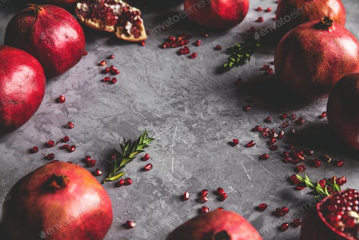 Pomegranate fruit. Ripe and juicy pomegranate on rustic grey background copy space for your text