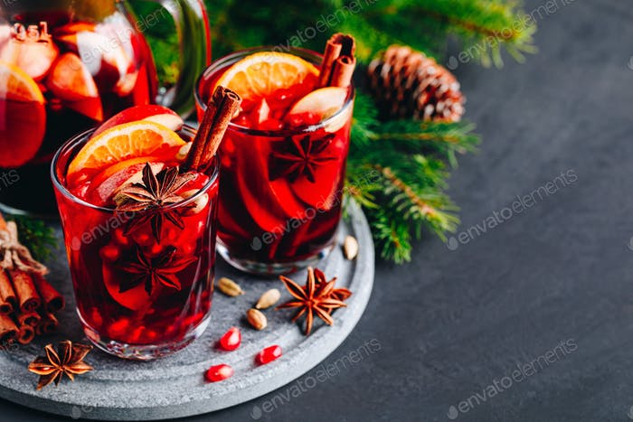 Christmas sangria or mulled wine with apples, oranges, pomegranate and cinnamon sticks.