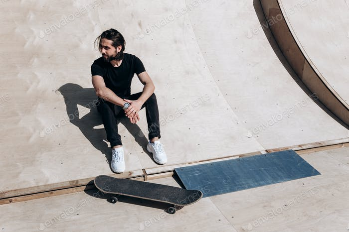 The man dressed in the stylish casual clothes is sitting on the slide next to the skateboard in a