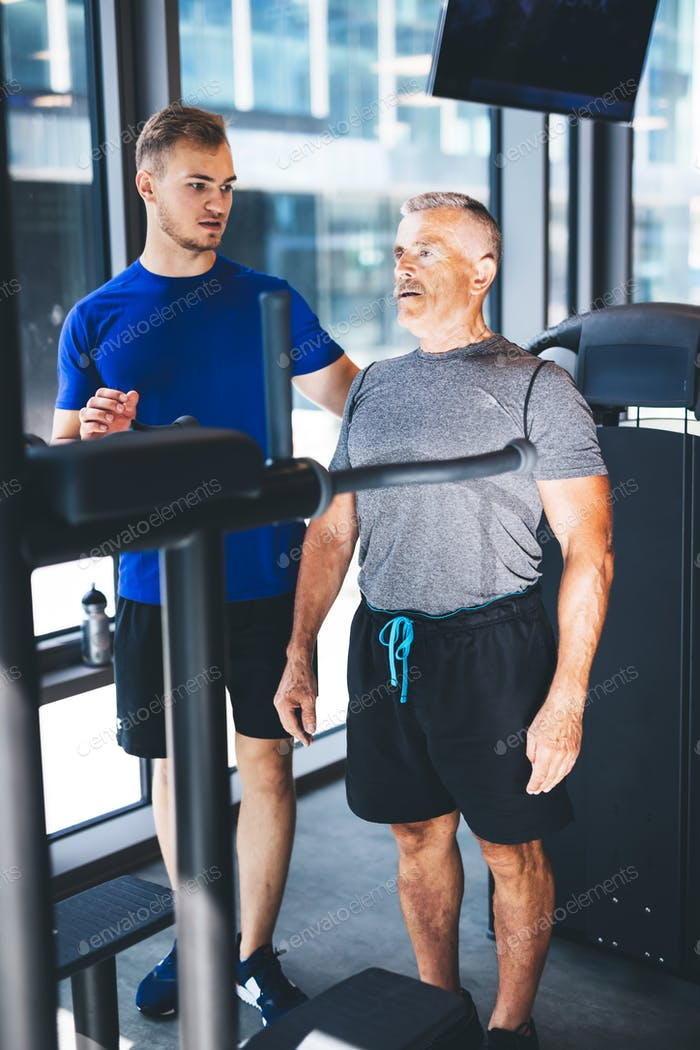 Personal trainer giving instructions to older man at the gym