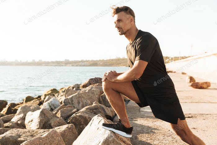 Portrait of a handsome sportsman doing stretching exercises
