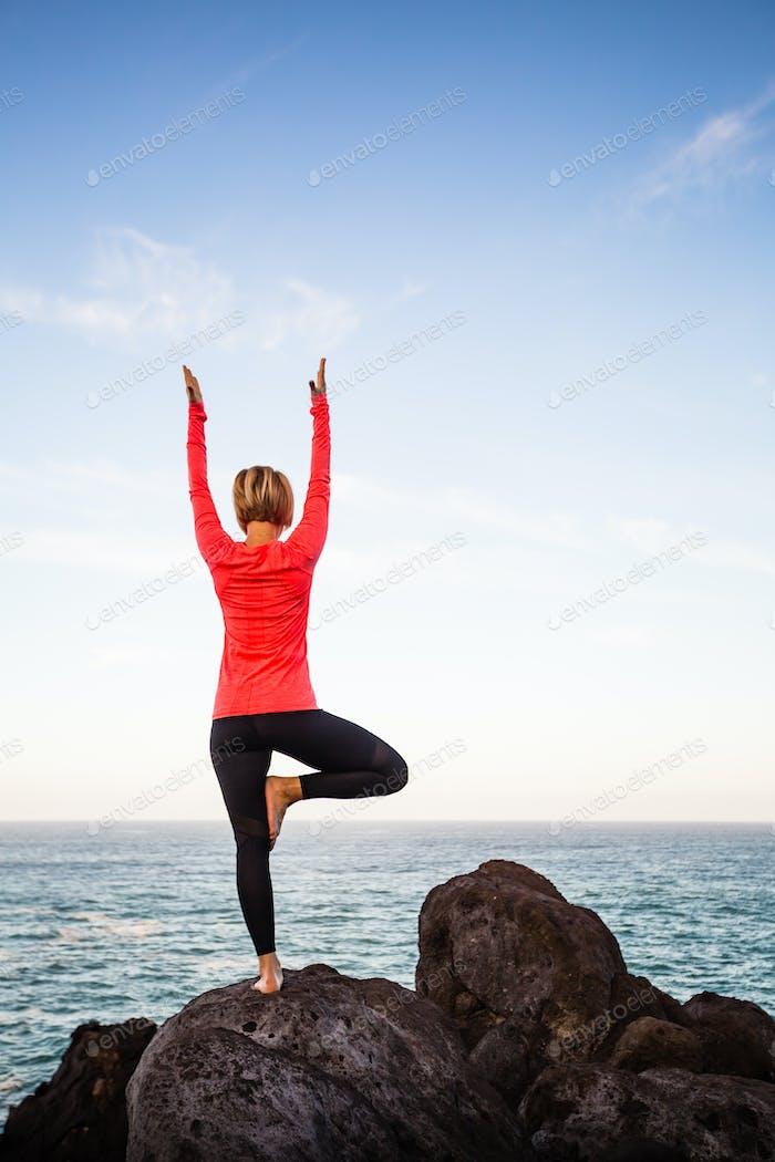 Yoga girl meditating in vrksasana tree pose