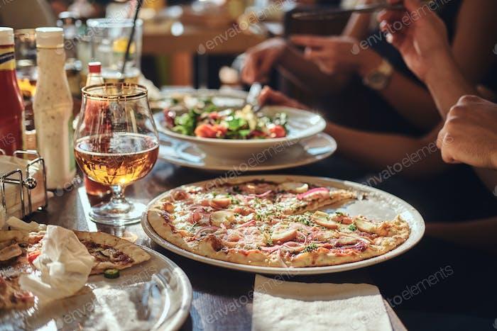 Junge Freunde Schüler essen Pizza und Salate in einem Outdoor-caf während der Mittagspause