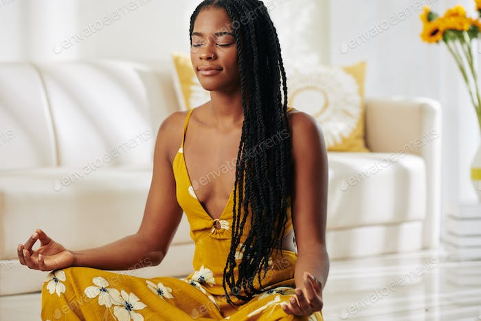 Pretty woman meditating at home