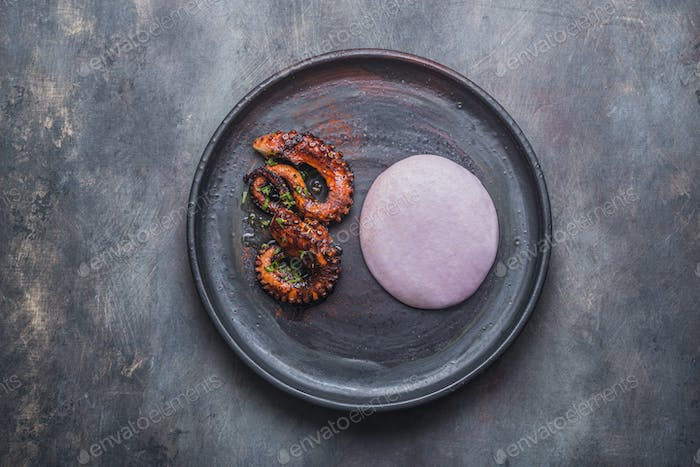 Grilled octopus tentacles with violet potato puree, reastaurant dish