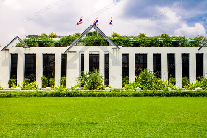 Asia botanic garden building exterior and green grass lawn with plant and flags on roof top