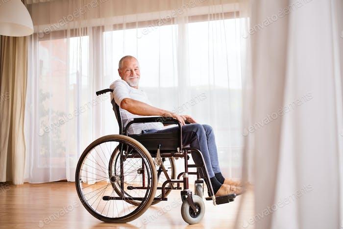 Senior man sitting on wheelchair at home.