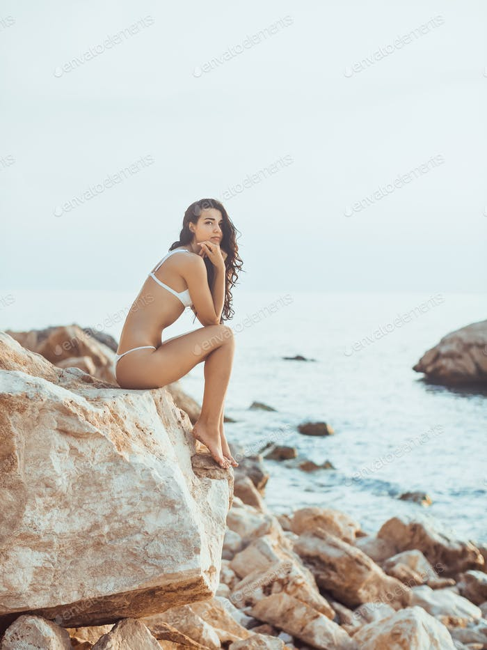Portrait of beautiful young woman on wild rocky beach