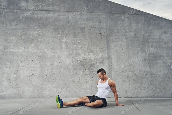Fitness athlete man relaxing and stretching muscles and legs