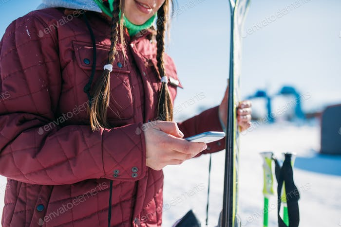 Female skier holds skis and mobile phone in hands