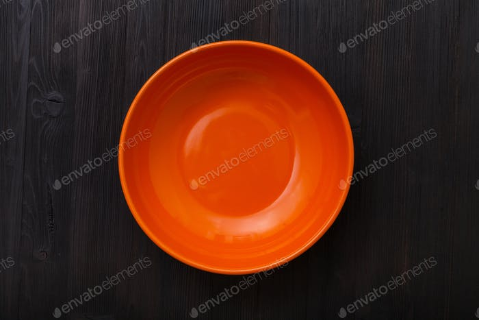 top view of orange bowl on dark brown table
