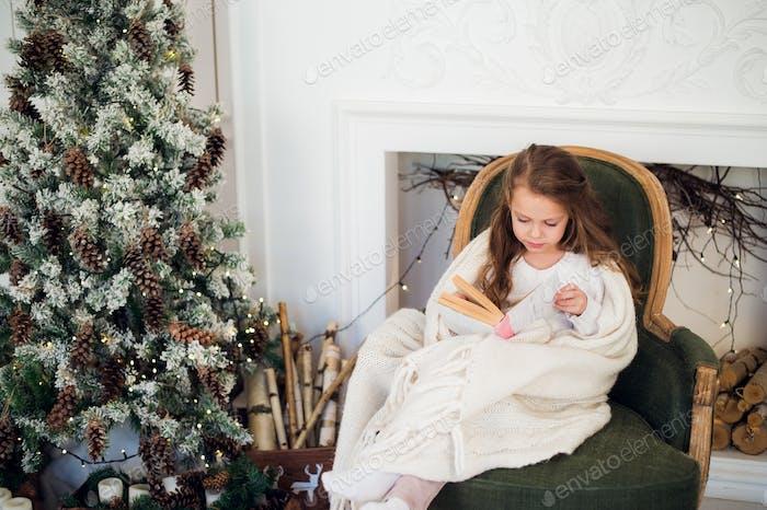 Kleines Mädchen Lesebuch in der Nähe von Weihnachtsbaum