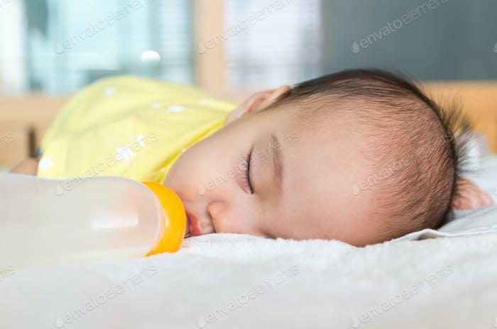 Asian baby sleeping and drinking milk