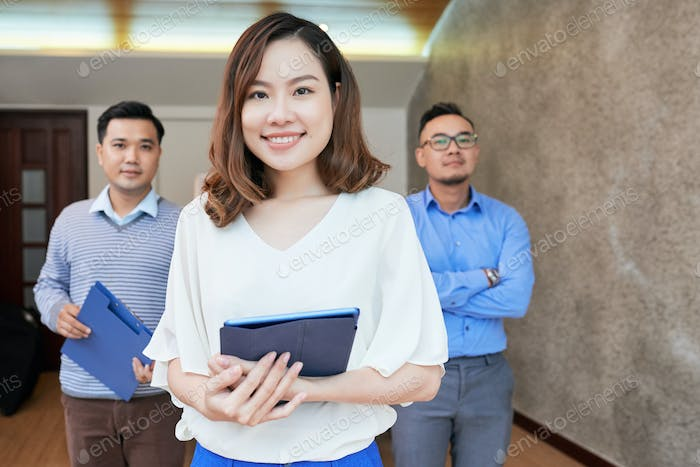 Beautiful ethnic woman with coworkers looking at camera
