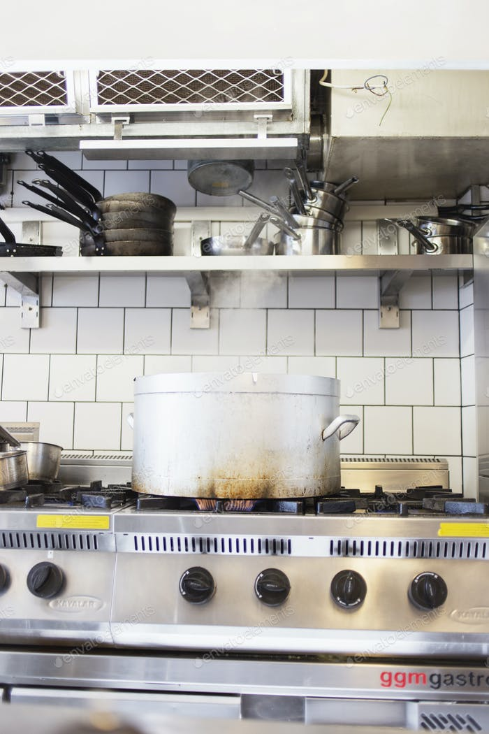 Metal container on stove at commercial kitchen