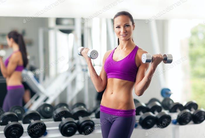 Молодая женщина делает упражнения с гантелями