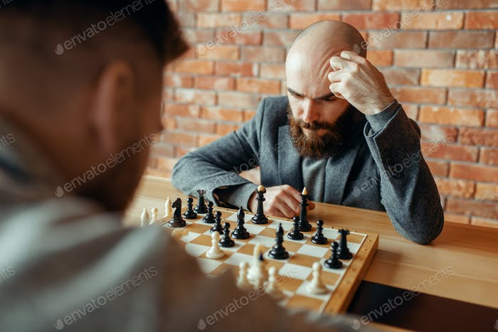 Male chess players playing, thinking process