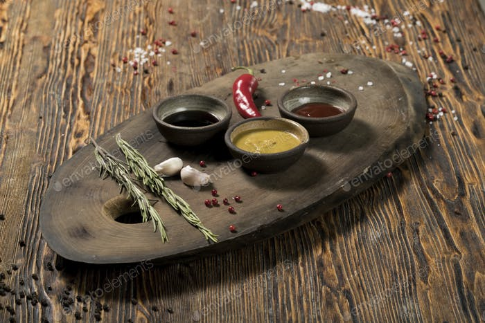 Various spices, herbs, garlic and sauces on a wooden background, studio lighting, top view