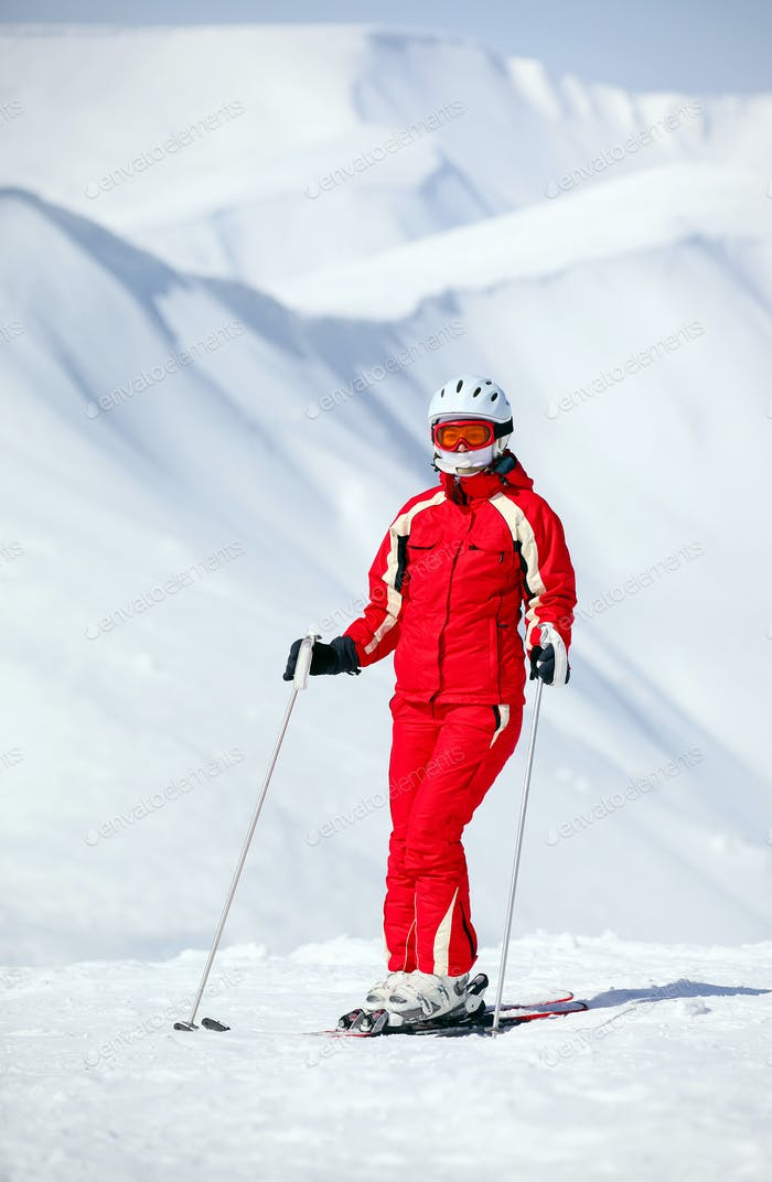 Female skier standing on mountain slope