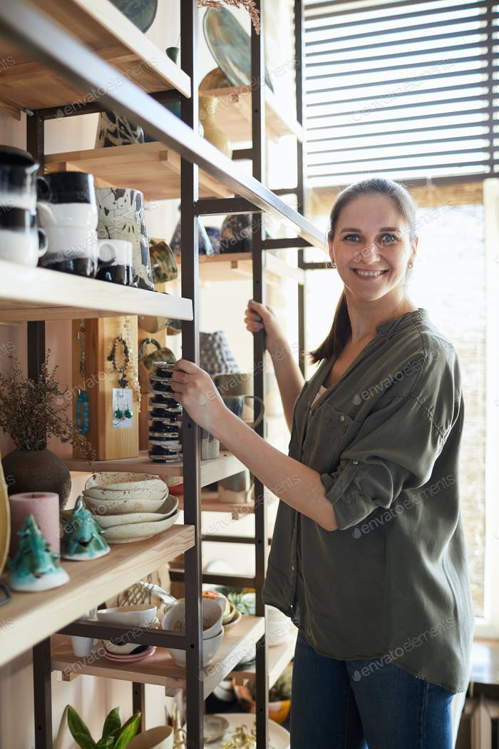Smiling Woman by Shelf with Ceramics