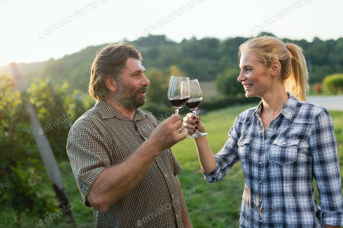 Wine growers toasting with red wine in vineyard