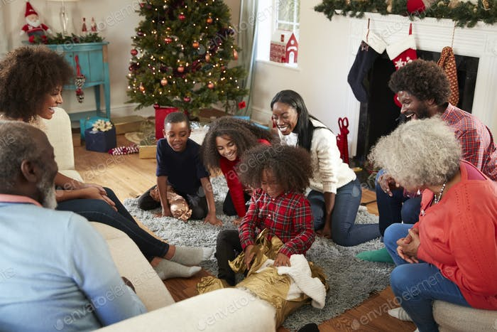 Son Opening Gift As Multi Generation Family Celebrate Christmas At Home Together