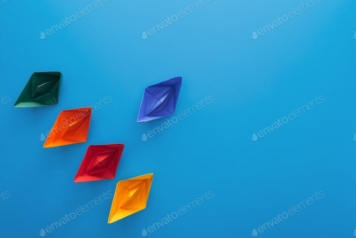 Flat lay with colorful paper boats on blue surface