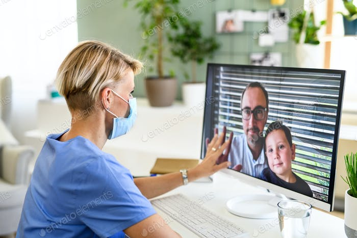 Woman doctor having video call with husband and son, social distancing concept