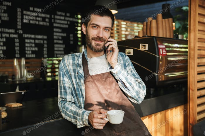 Portrait of young barista guy talking on cellphone in street caf