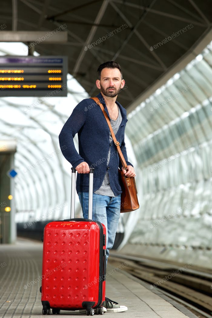 Mature man standing on train station platform with bag