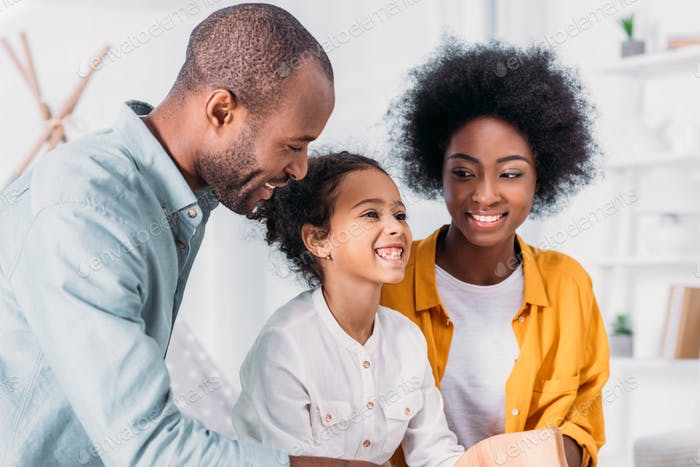 smiling african american parents and daughter having fun at home