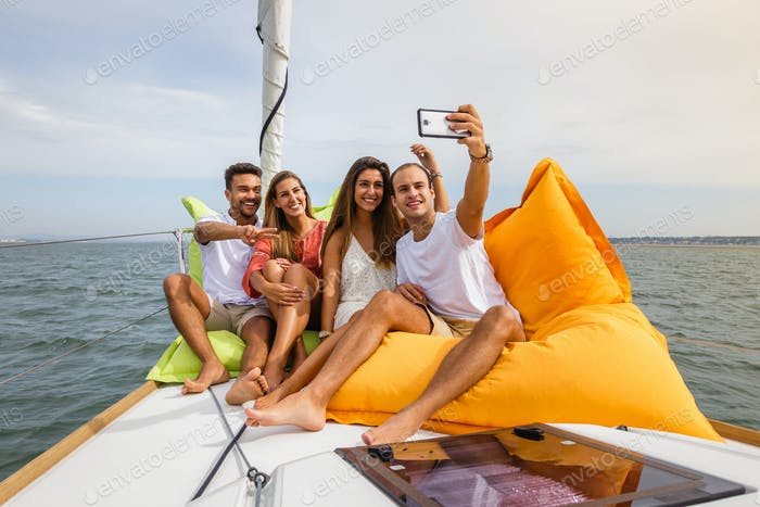 Group of friends having fun in boat in river