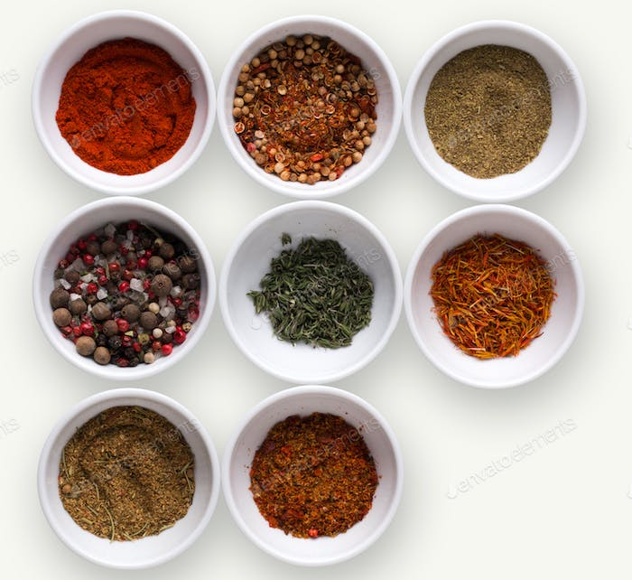 Diverse spices in plates on dark background, closeup, copy space