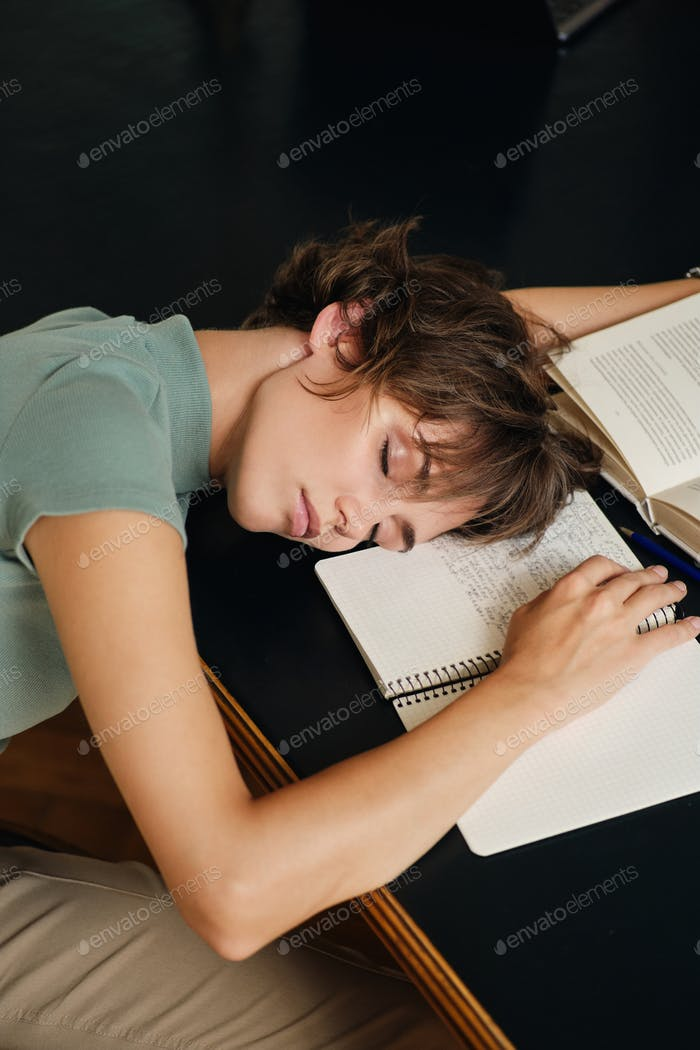Tired student girl sleeping on desk with book and abstract during study in library of university