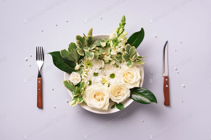 White flowers on plate, fork, knife over grey background. Healthy eating, vegan diet concept