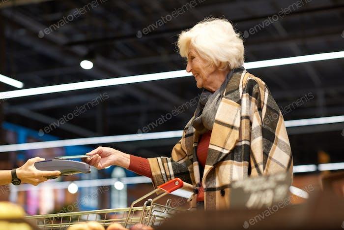 Senior Woman Using NFS in Supermarket