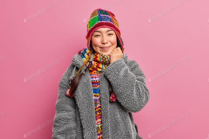 Pleased Asian woman wears warm knitted hat scarf and fur coat smiles happily has tender face express