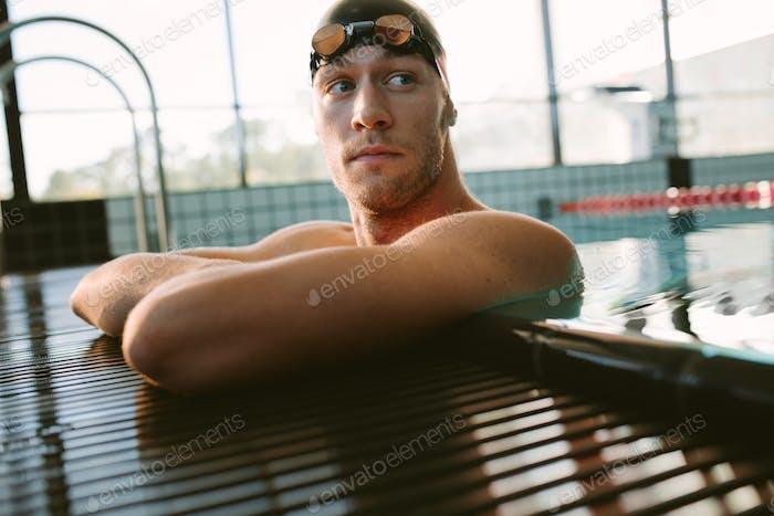 Männliche Schwimmer ruht auf dem Rand des Swimmingpools