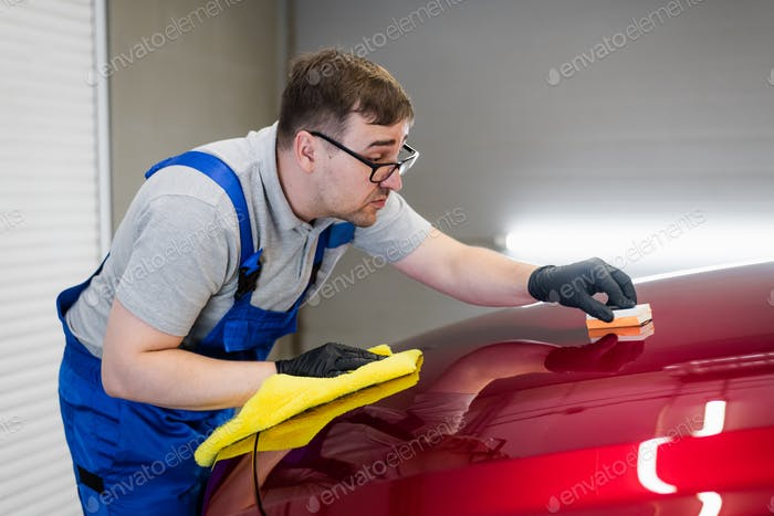 Man worker of car detailing studio applying ceramic coating on car paint with sponge applicator