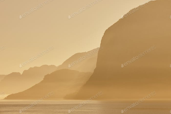 Norwegian fjord landscape at dawn in warm tone. Norway highlight. Horizontal