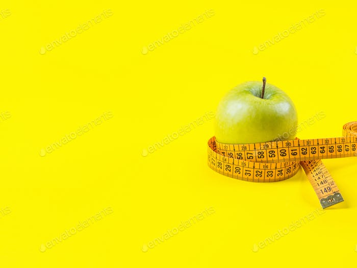 Green apple with measuring tape on yellow