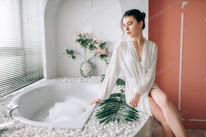 Beautiful woman sitting on the edge of the bath