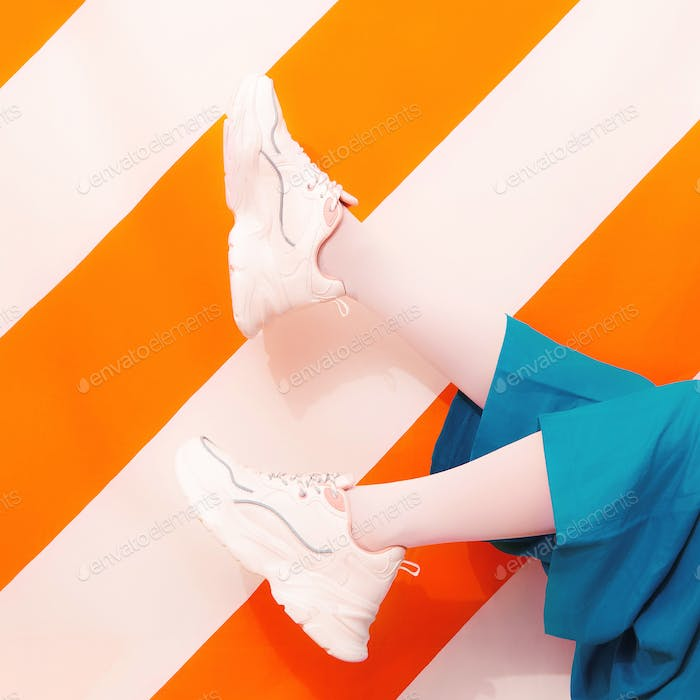 Unrecognizable girl in white sneakers on trendy yellow striped background