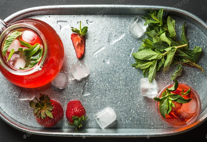 Homemade strawberry lemonade, mint and ice, served with fresh berries in metal tray, top view