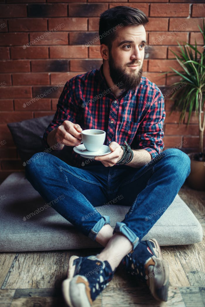 One bearded man drinks coffee in cafe